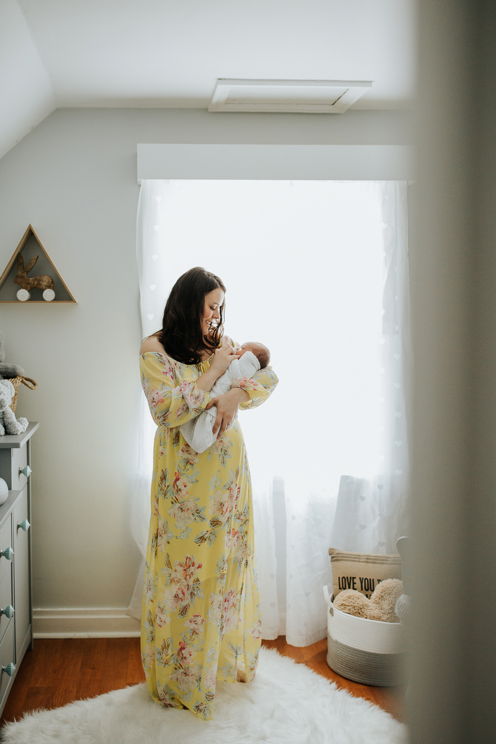 new mom standing in nursery in front of window rocking 3 week old baby boy in white swaddle to sleep - Stouffville Lifestyle Photos
