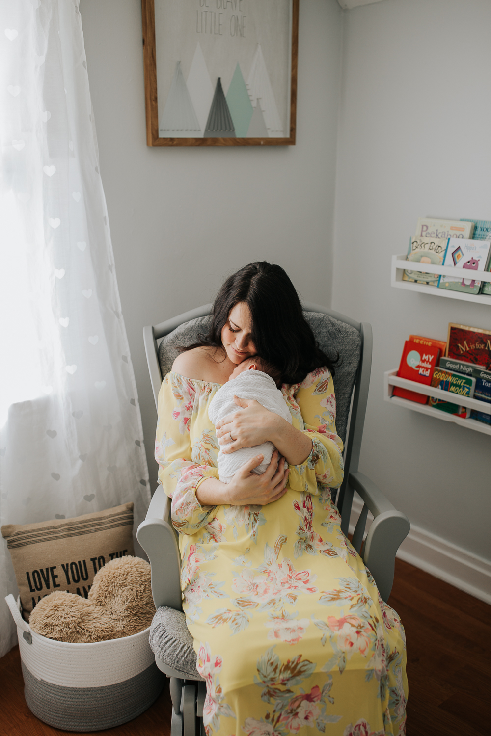 new mother sitting in nursery rocker snuggling 3 week old baby boy on her chest, mom's chin resting on son's head - Barrie Lifestyle Photography