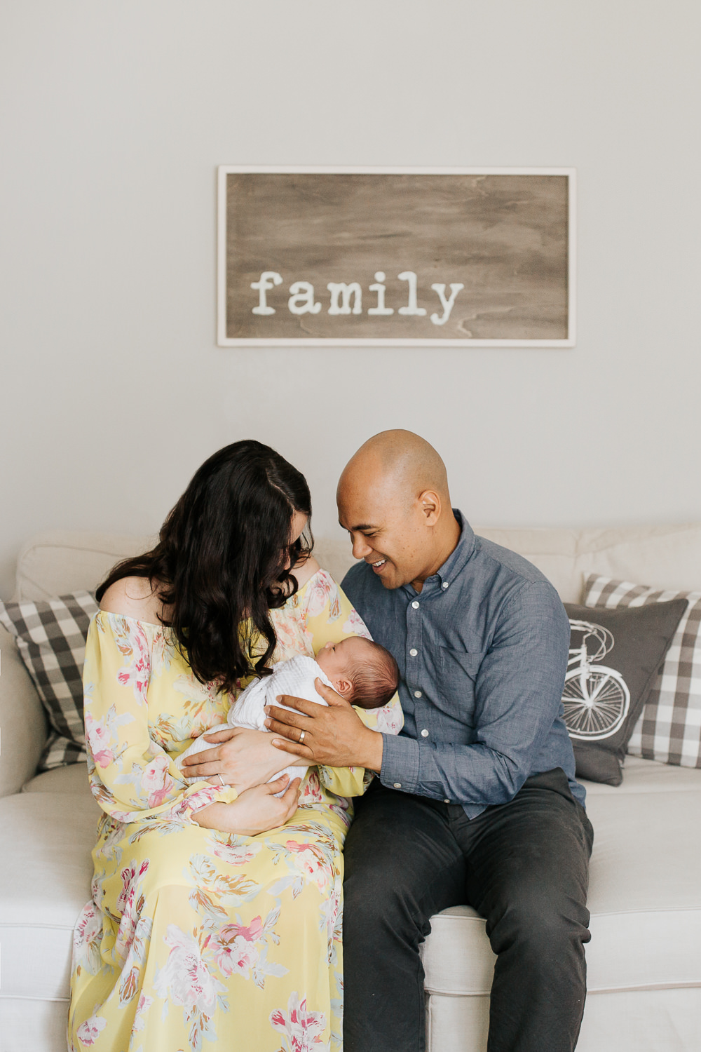 new parents sitting on couch, 3 week old baby boy in mother's arms, father hand on son, smiling - GTA Lifestyle Photography