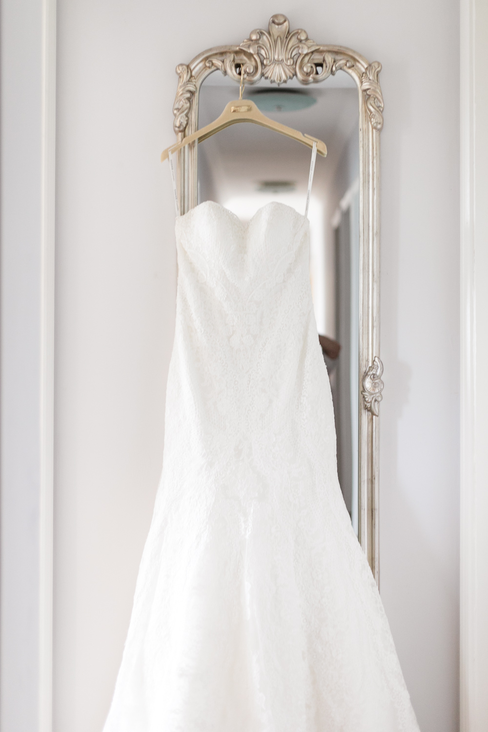 White wedding dress hanging on a vintage mirror