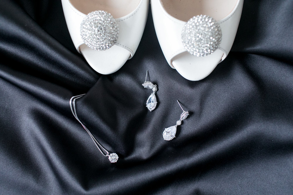 White wedding shoes with wedding jewellery on black silk garment
