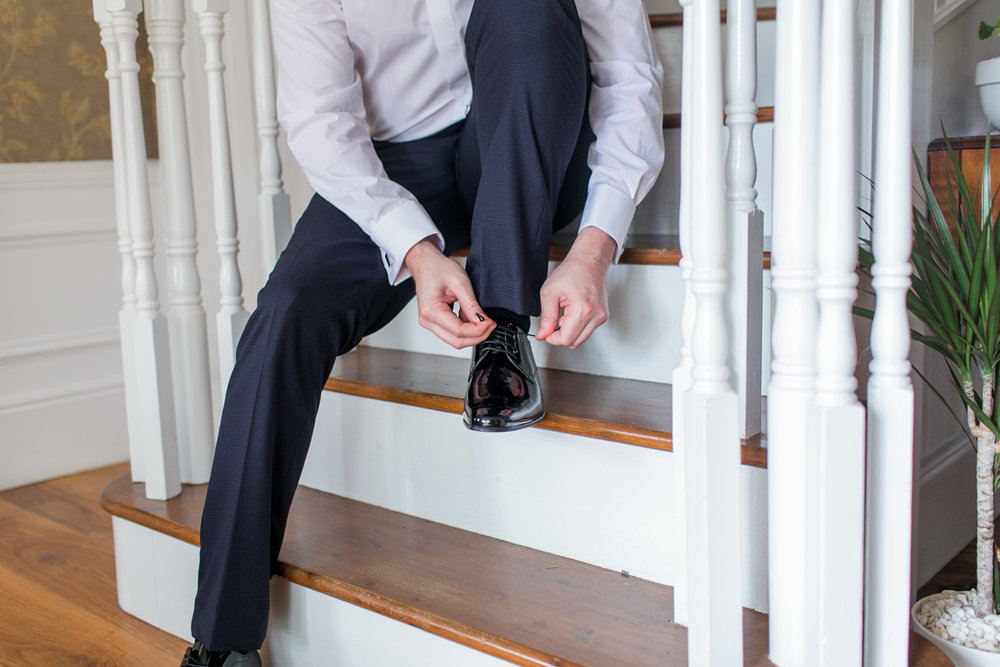 Groom on the stairs putting on his black patent shoes tying his laces