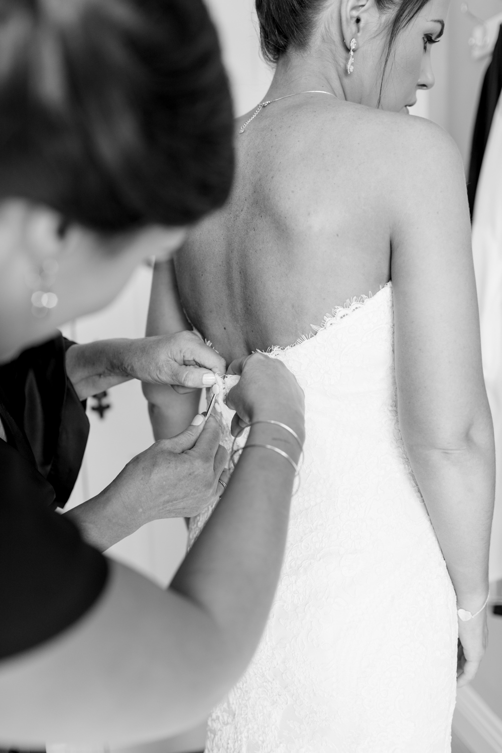 bride's mother helping her to put on the dress buttoning the buttons behind