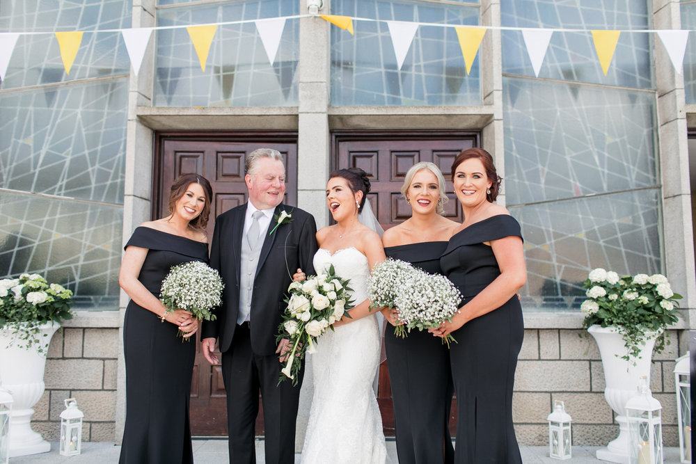bride with her bridesmaids dressed in black and her dad outside the church before the wedding ceremony