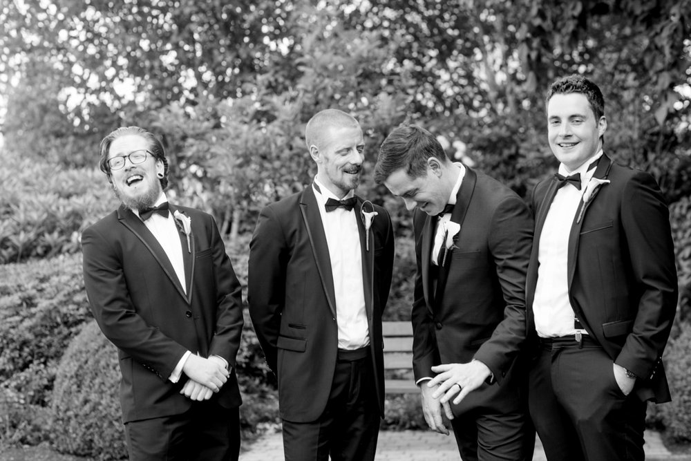 groomsmen with the groom laughing at the camera in black tux suits at slieve russell hotel in ireland