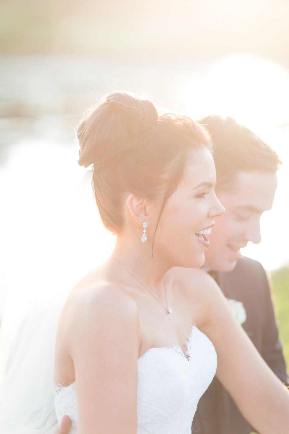 bride laughing in the warm evening light on her wedding day with an upstyle hairstyle and an open shoulder wedding dress