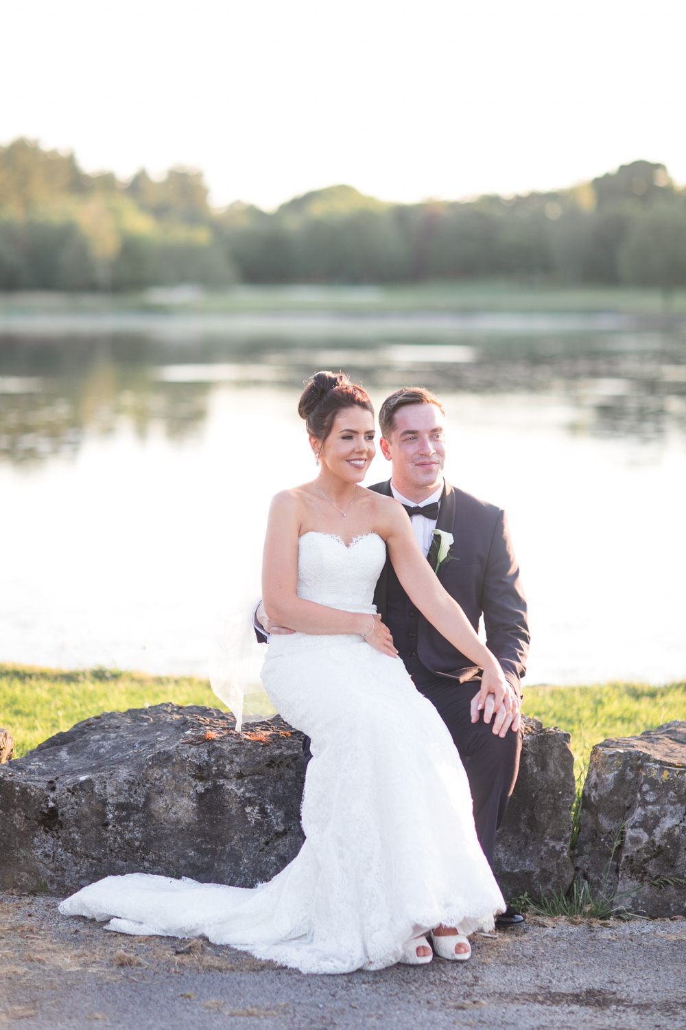 bride and groom sitting on the edge of the lake with the evening light at slieve russell hotel in ireland