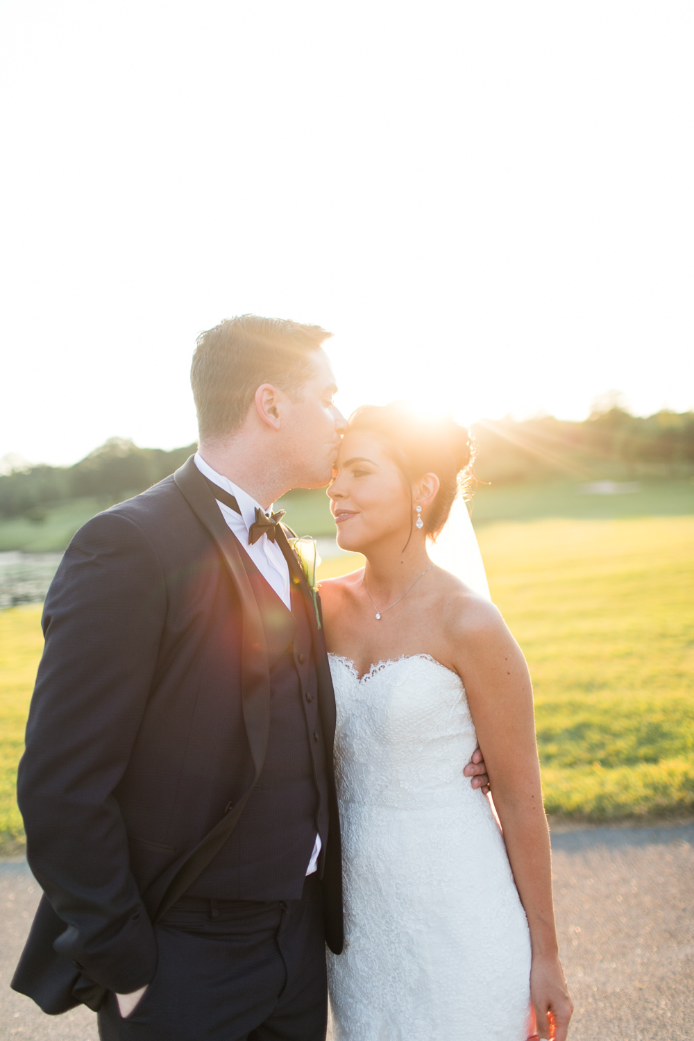 bride and groom kissing in the sunset on the grounds of slieve russell groom wearing a black tux