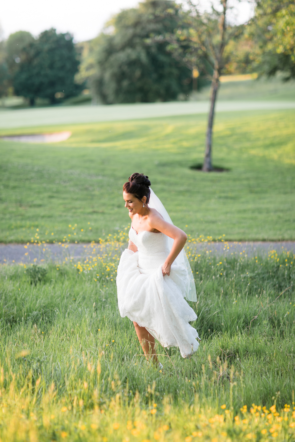 bride walking in the meadow in evening light holding up her mermaid open shoulder dress in sliever ussell hotel in ireland