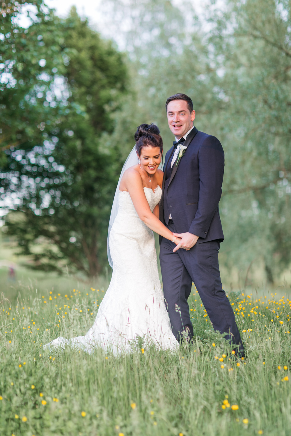 bride laughing beside her groom in a meadow full of yellow flowers
