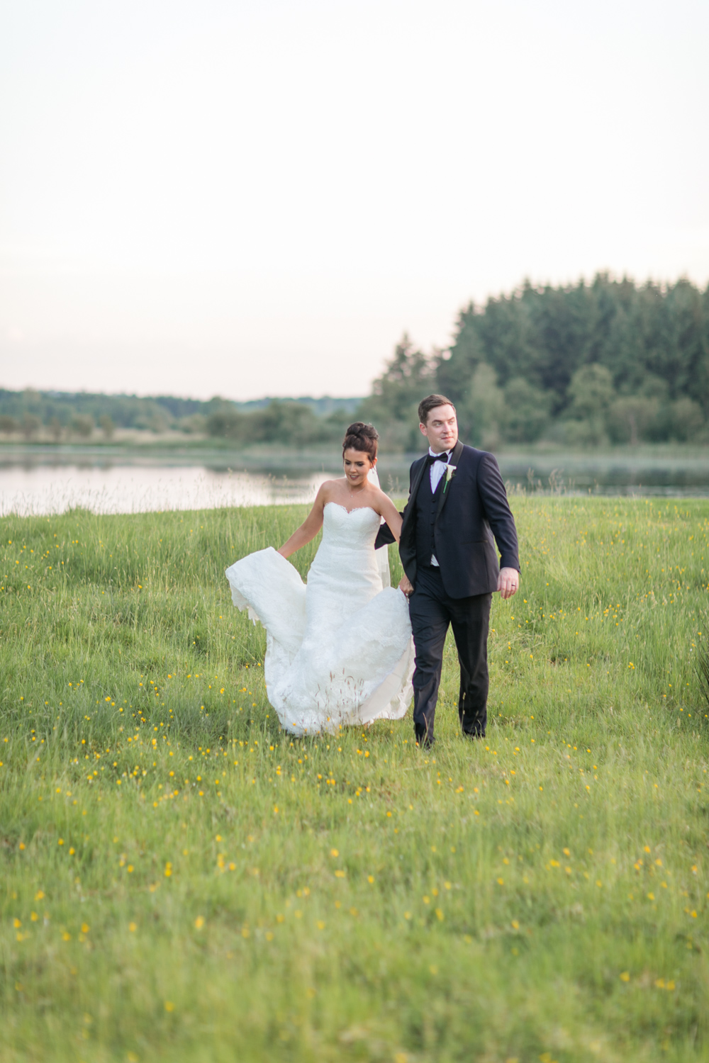 bride and groom walking in the meadow with lake in the background in the evening at slieve russell hotel in ireland