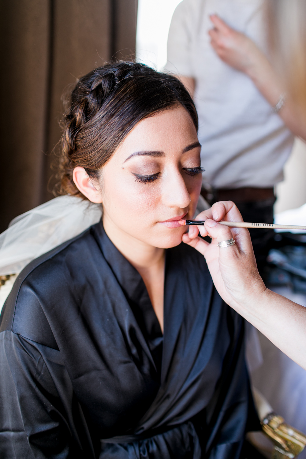 bride getting ready in a black silk robe