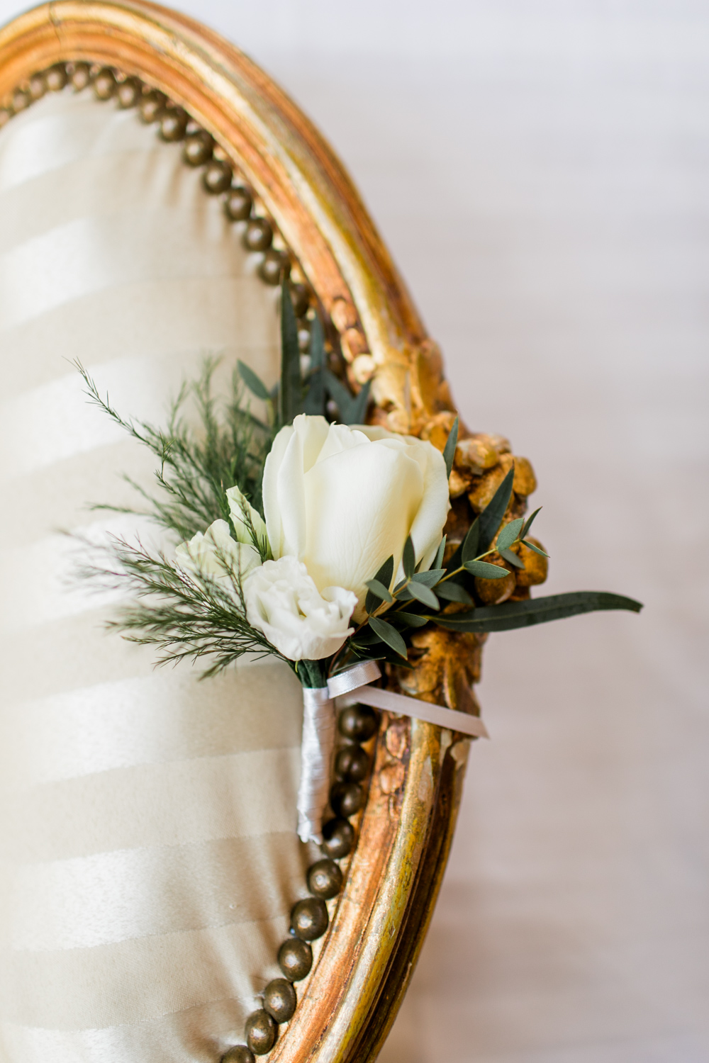 buttonhole made out of a white rose an a butter cup on top of a vintage hotel chair
