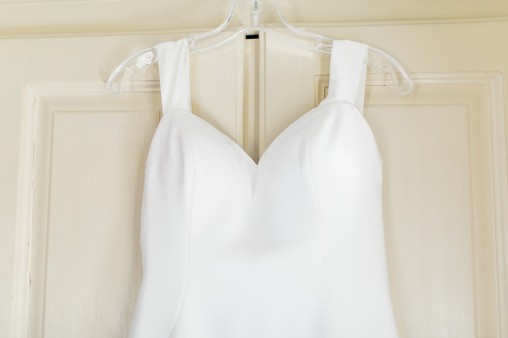 a close up of a sweetheart wedding dress hanging on a white vintage wardrobe