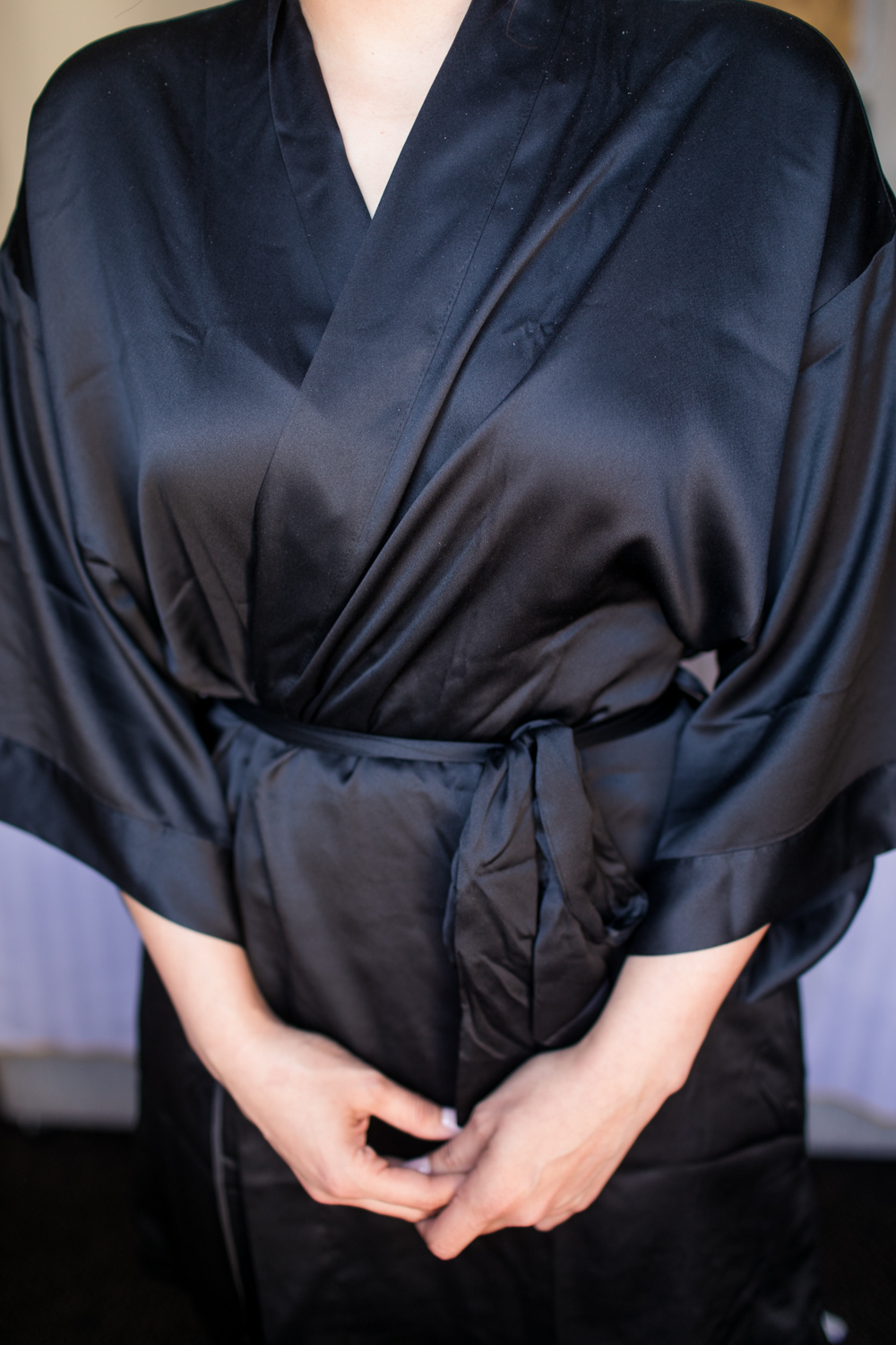 a close up of a bride in her black silk robe while getting ready for a wedding day