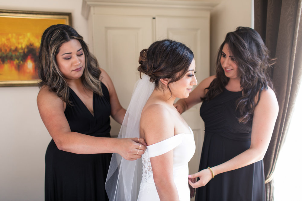 bride surrounded by bridesmaids helping her put on her wedding dress bridesmaids are wearing black dresses