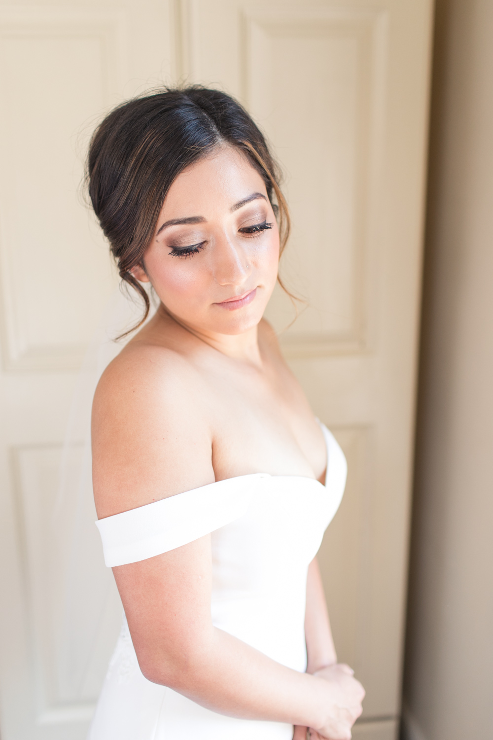 bridal portrait while she is getting ready showing off her light pink eyeshadow and an up style hairstyle with an off shoulder wedding dress