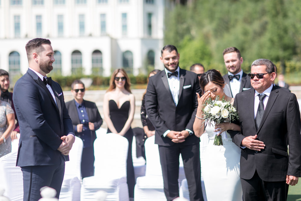 bride seeing her husband crying while being escorted by her dad