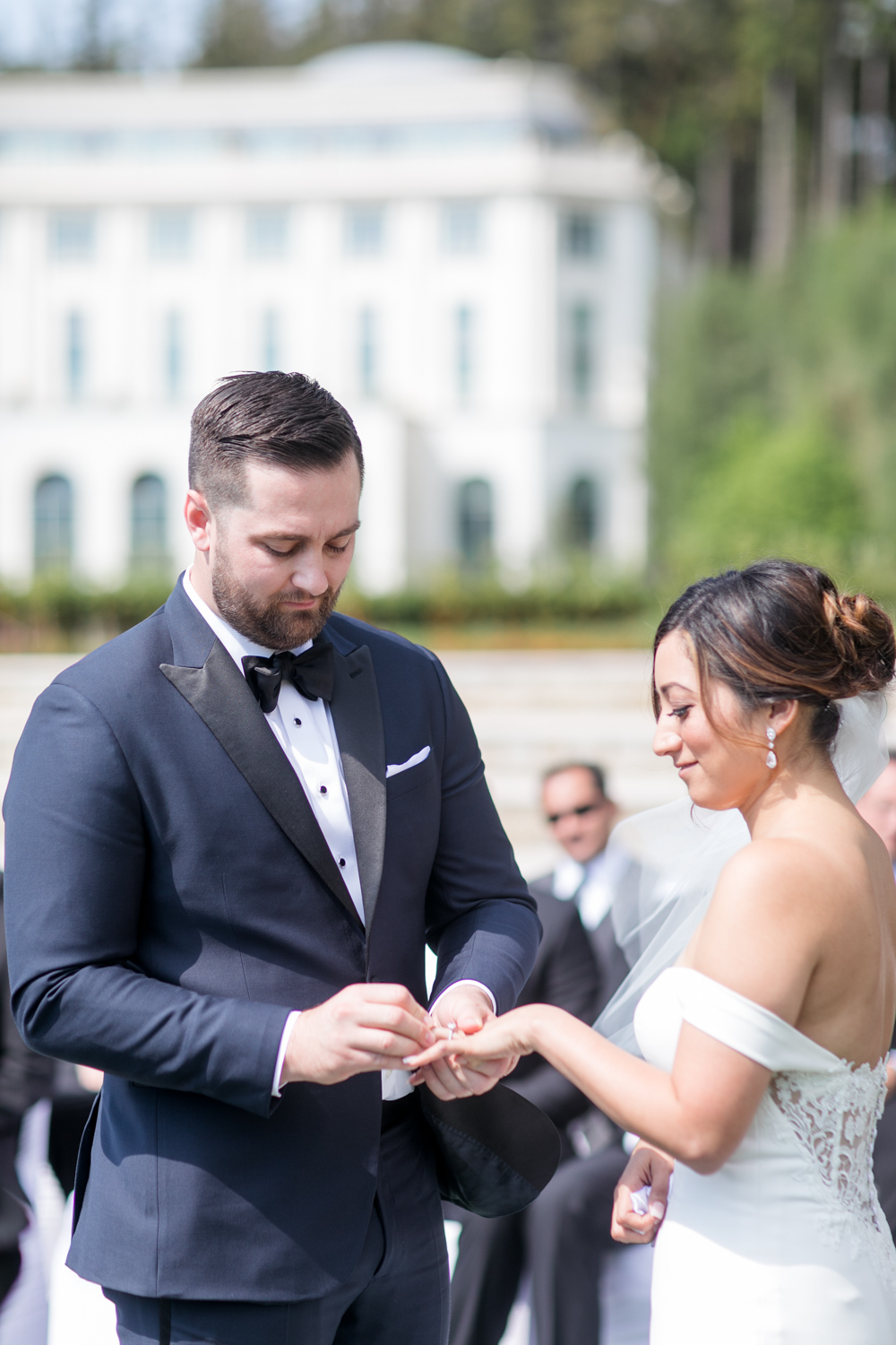 powerscourt hotel ceremony outside groom in black tie tux putting on a wedding ring on his bride's hand