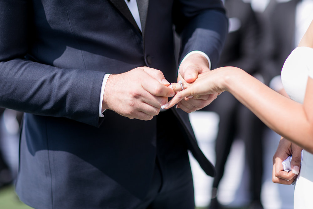 the close up of a groom putting on a ring on his bride's hand