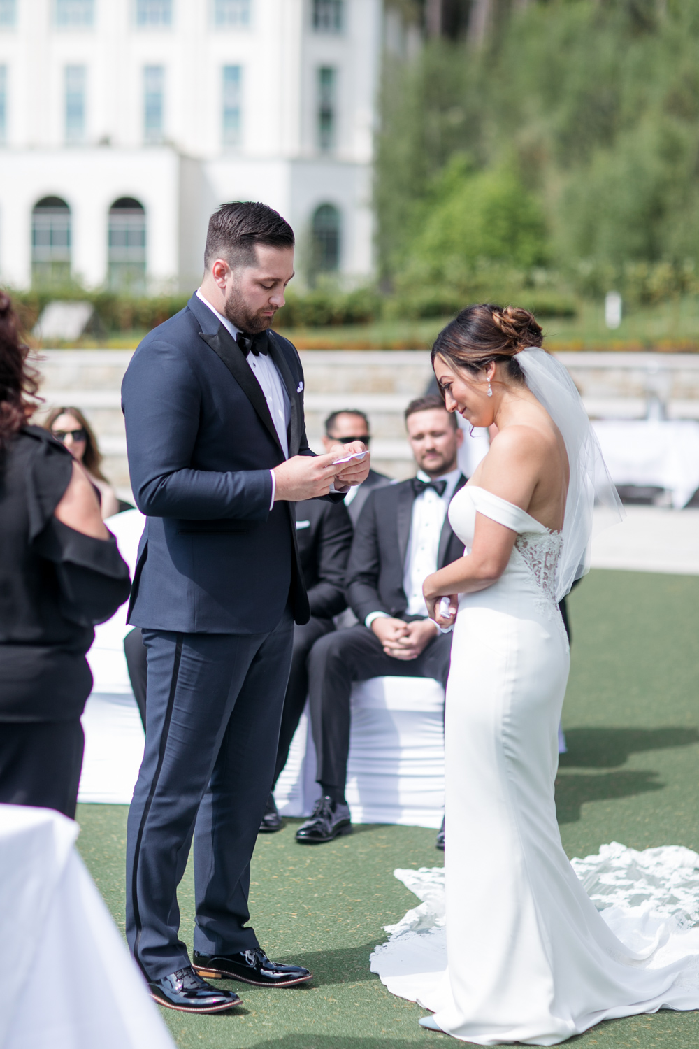 groom is saying his vows outside the powerscourt hotel in wicklow ireland wearing a black tux