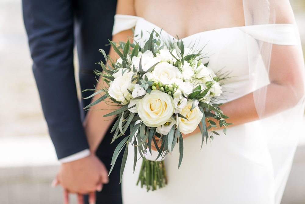 close up of bride and groom holding hands and in one of the bride hands a rose and buttercup wedding bouquet