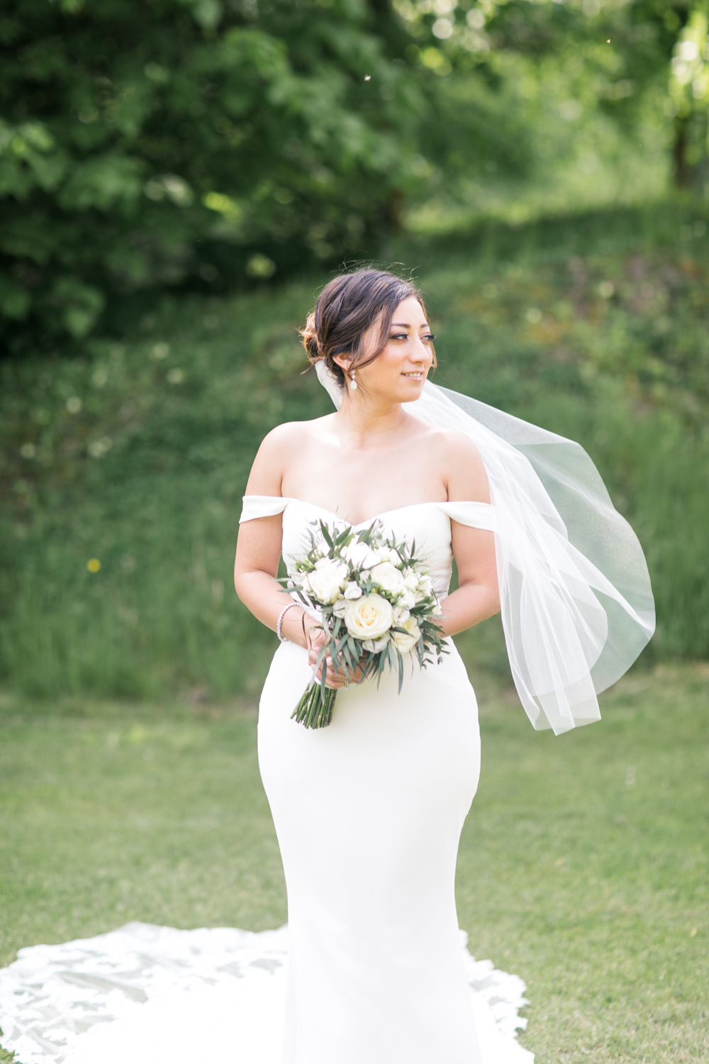 bride standing alone wearing a plain wedding dress with a large train and a short veil holding a white bouquet of wedding flowers