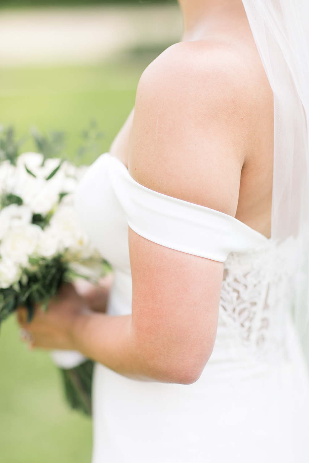 a close up of bride's shoulders holding a bouquet wedding dress is off shoulder