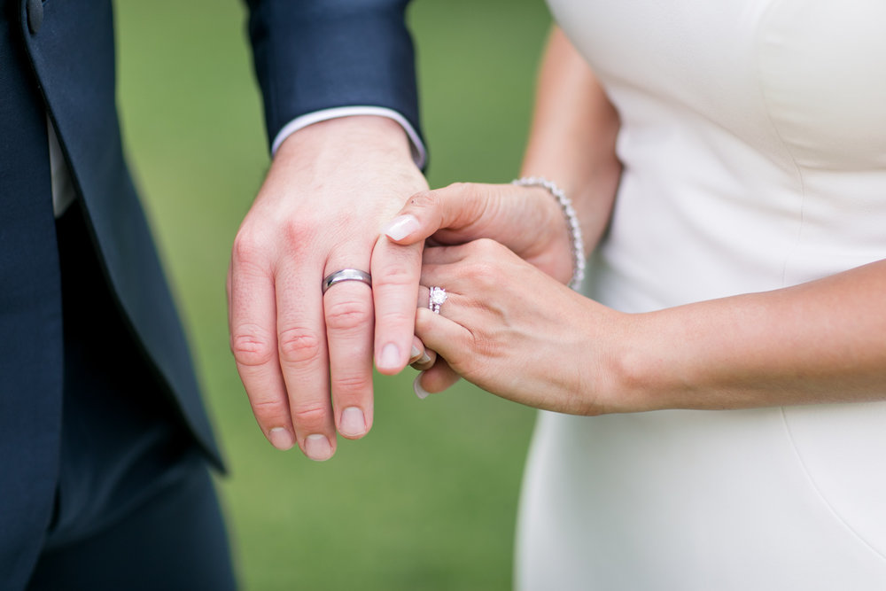 close up of bride and groom wedding rings intertwined in their hands holding each other