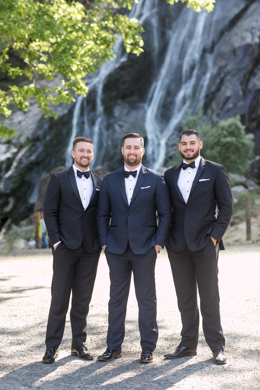 groom and his groomsmen posing in black tuxes in front of powerscourt waterfall in ireland