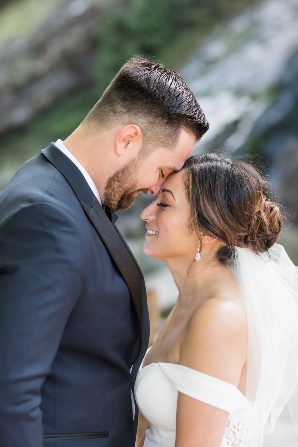 bride and groom standing side by side touching foreheads with big smiles