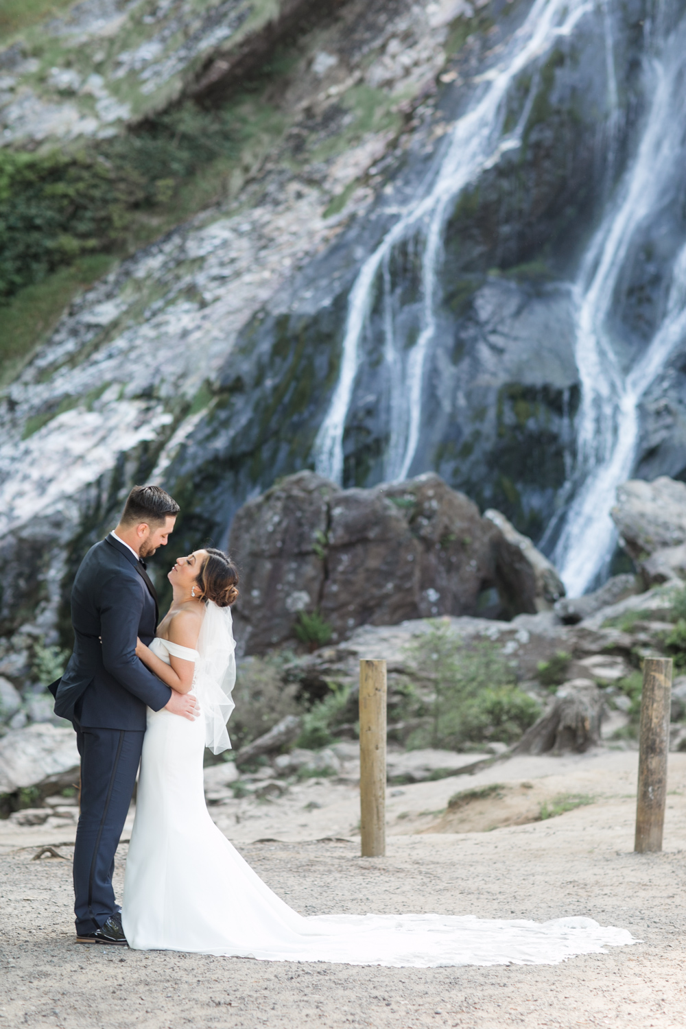 Bride and groom in front of the powerscourt waterfall in wicklow ireland on a sunny summer afternoon