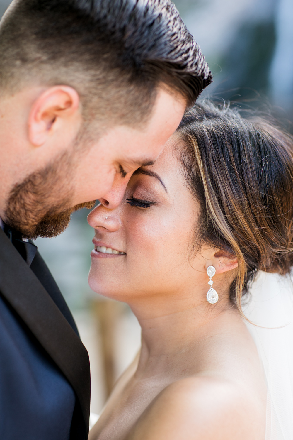 a close up of bride and groom touching foreheads smiling with their eyes closed
