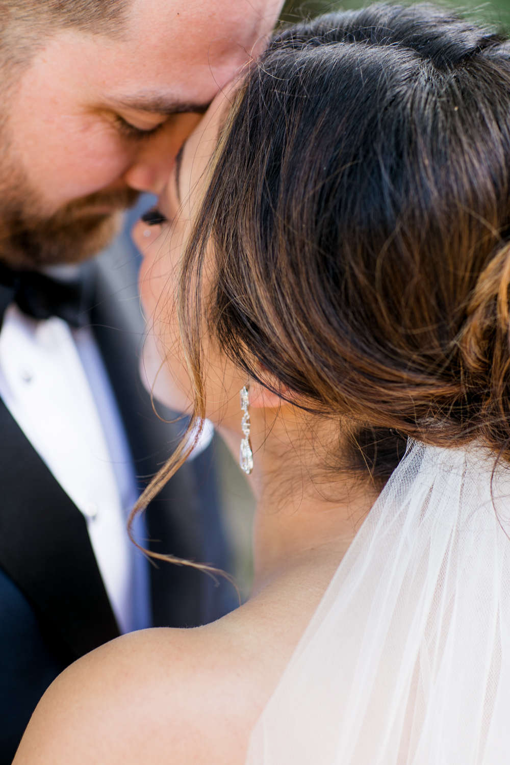 a close up of bride and groom close together with a focus on the bride's earring