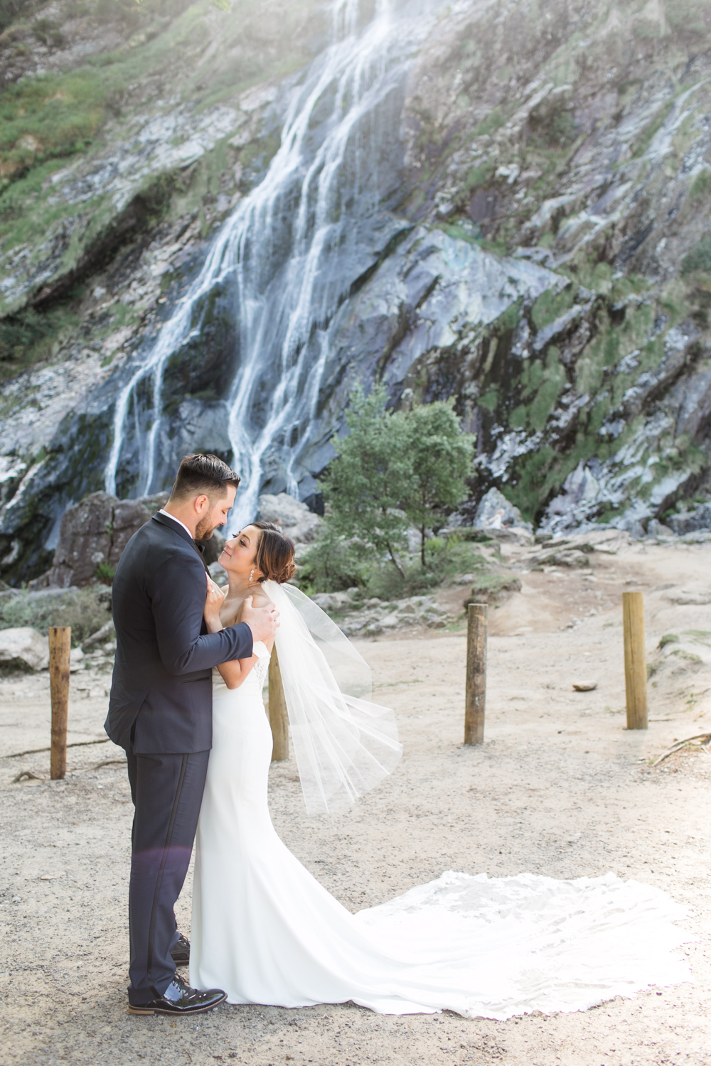 bride and groom in front of a waterfall in powerscourt wicklow ireland wearing an off shoulder white dress and a black tux