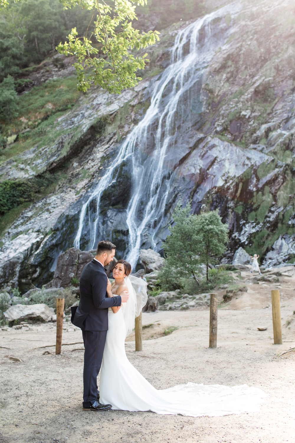 bride and groom looking up at each other with a big waterfall behind them they are located in powerscourt waterfall in wicklow, ireland