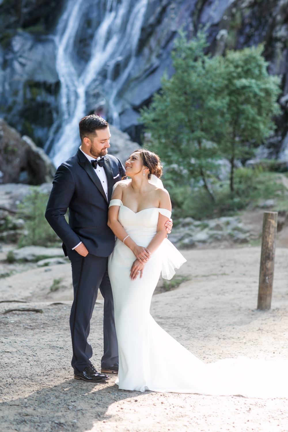 bride and groom looking up at each other with a waterfall behind them wearing a navy tux and an of shoulder plain elegant wedding dress in ireland