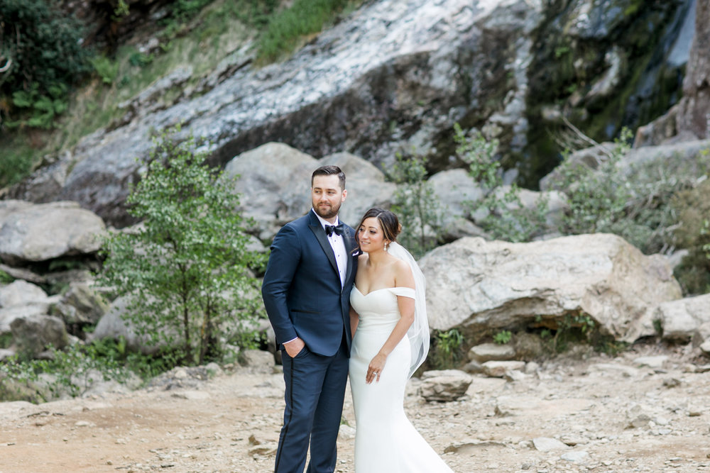 rocky background of irish powerscourt waterfall in wicklow with bride and groom wearing black tie wedding gowns