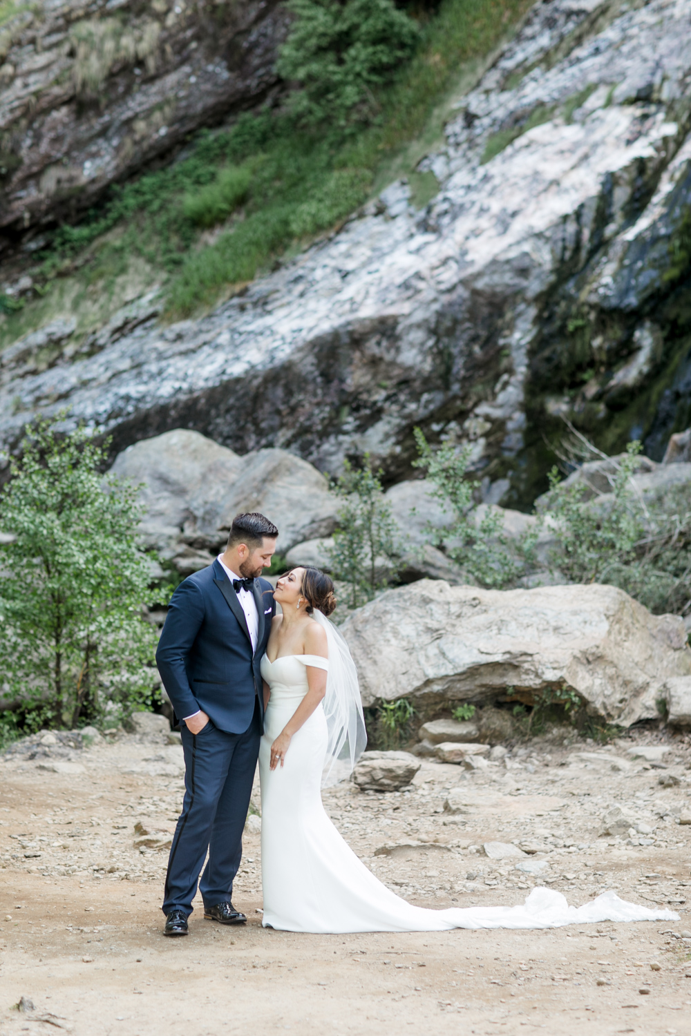 bride and groom looking at each other groom is wearing a dark navy tux and bride has a plain elegant wedding dress in front of a powerscourt waterfall in ireland