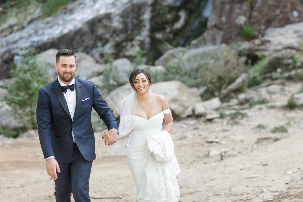 bride and groom on their elopement in ireland bride is walking holding up her plain off shoulder black tie wedding dress and groom wearing a dark navy tux
