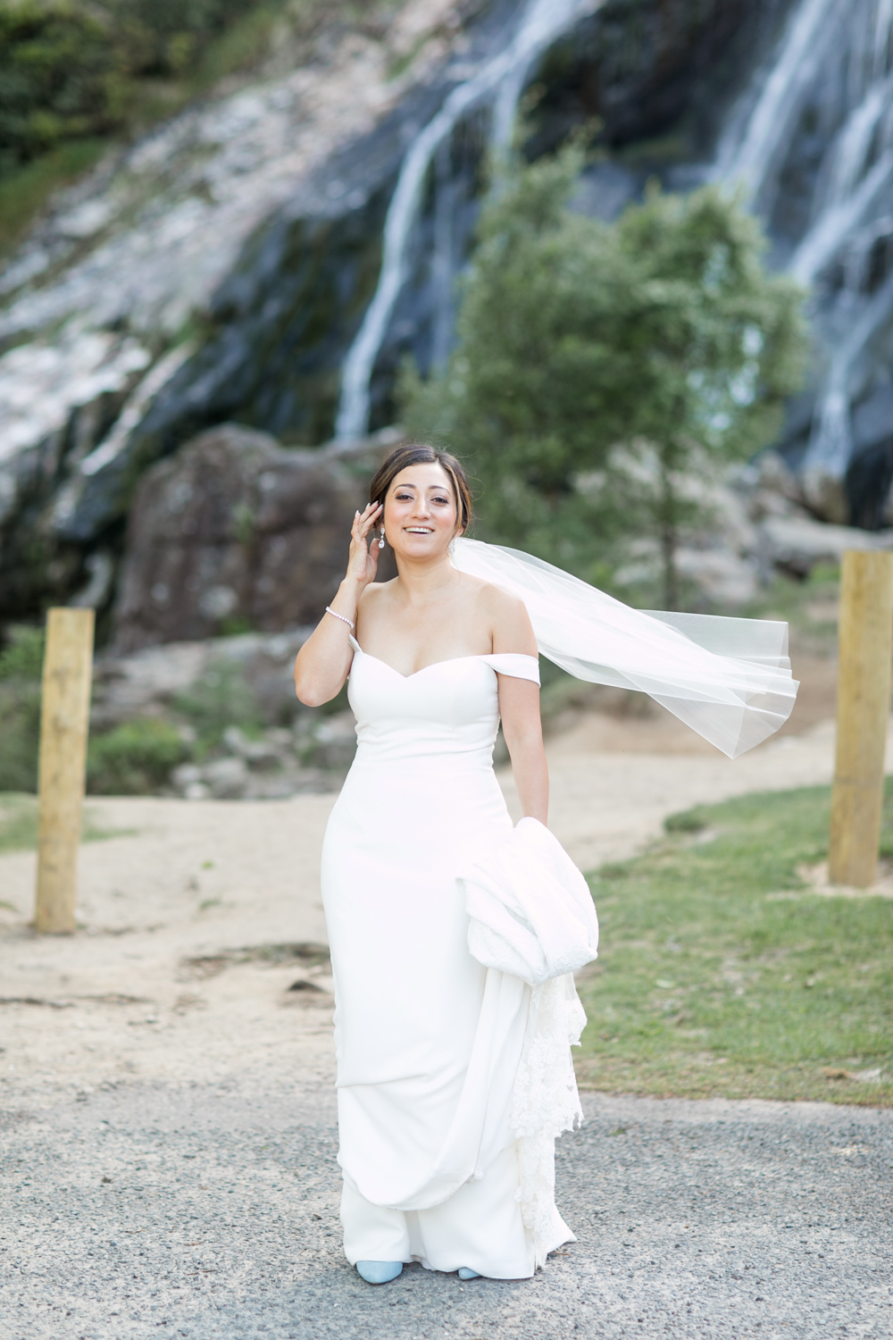 portrait of the bride standing with a powerscourt waterfall in the background holding up her simple off shoulder wedding dress train