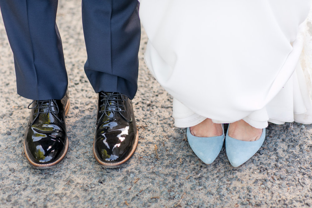 close up of bride and groom shoes bride is wearing light blue velvet michael kors shoes