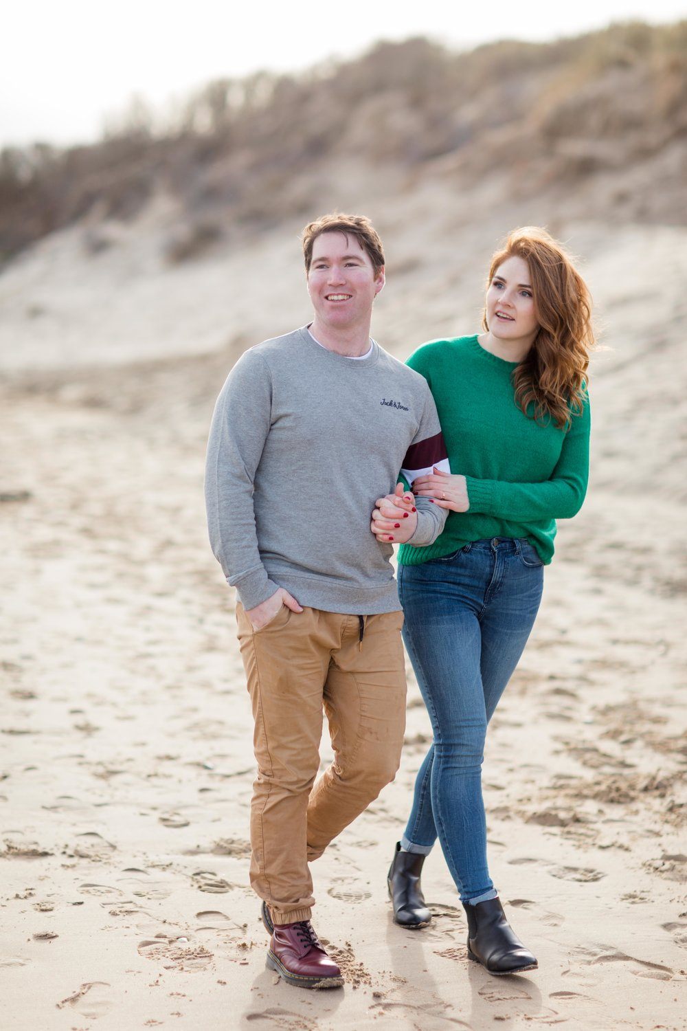 a photoshoot of a couple walking on a sandy beach in brittas bay wearing a green jumper and jeans with red hair and khaki chinos and a grey jumper