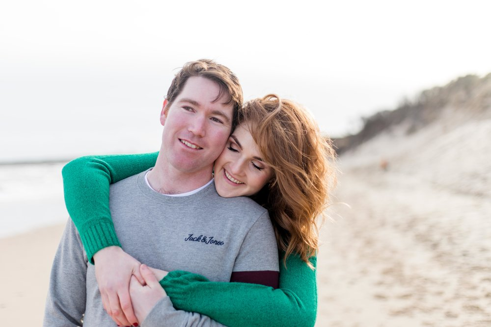 an engagement photoshoot of a couple posing on a sandy beach a woman with red hair and a green jumper and a man wearing a grey jumper in brittas bay in ireland
