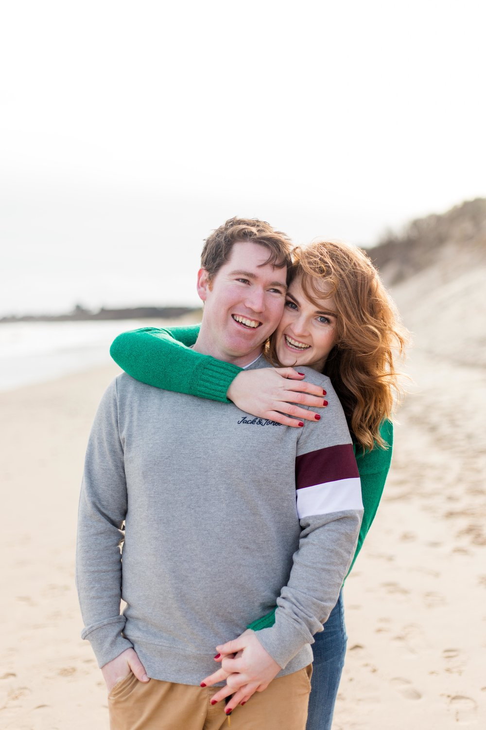 a couple posing for an engagement photoshoot on a sandy beach brittas bay in ireland a woman has red hair and is wearing a green jumper and a man is wearing a grey jumper with khaki chinos