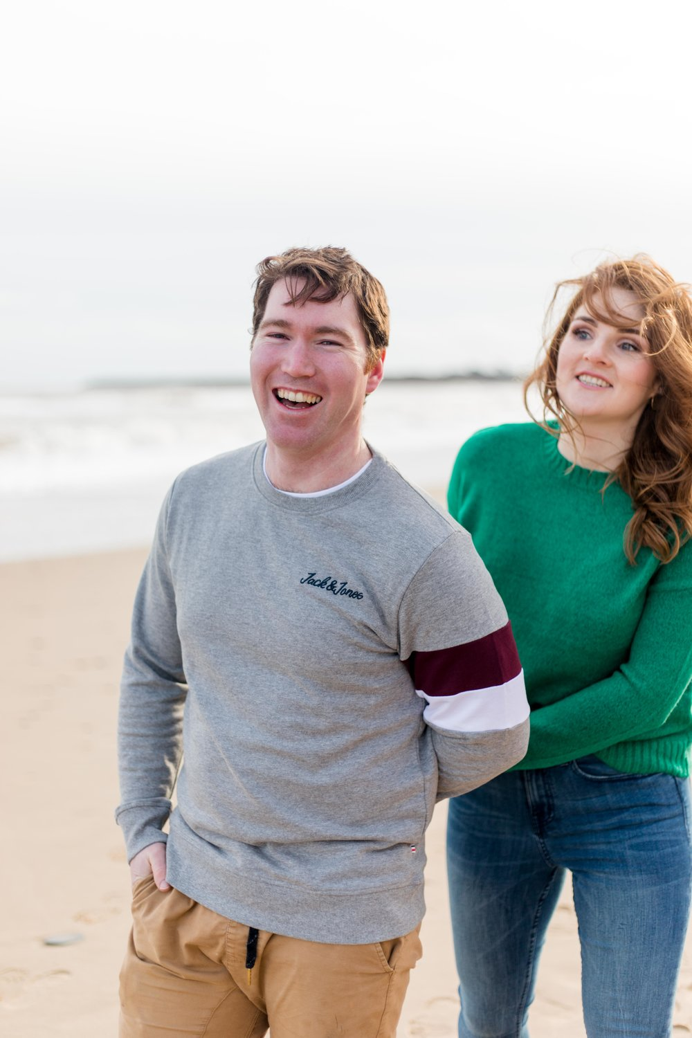 a photoshoot of a couple holding hands and laughing posing for an engagement shoot at brittas bay in ireland woman wearing red jumper with red hair and man wearing khaki chinos and a grey jumper
