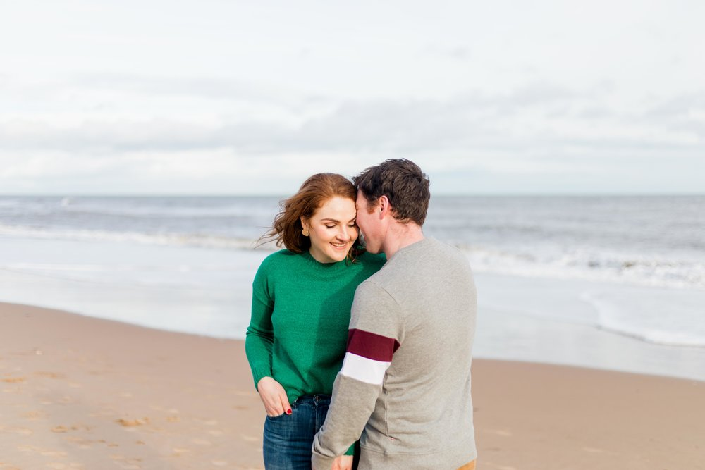 man wearing grey jumper and woman green jumper and blue jeans with red hair snuggling on a sandy beach for a photoshoot in ireland