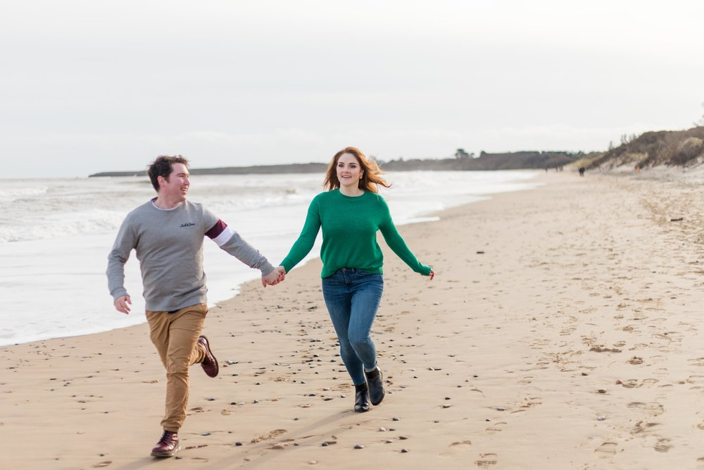 a man and a woman holding hands running on a sandy beach in brittas bay ireland woman wearing green jumper with red hair and blue jeans and man wearing khaki chinos and grey jumper