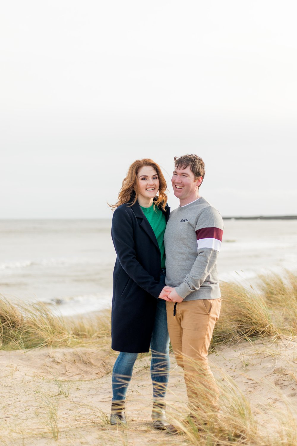 an engagement shoot of a couple on a hill of a sandy beach at britas bay in ireland woman wearing black coat and green jumper with red hair and black boots and blue jeans