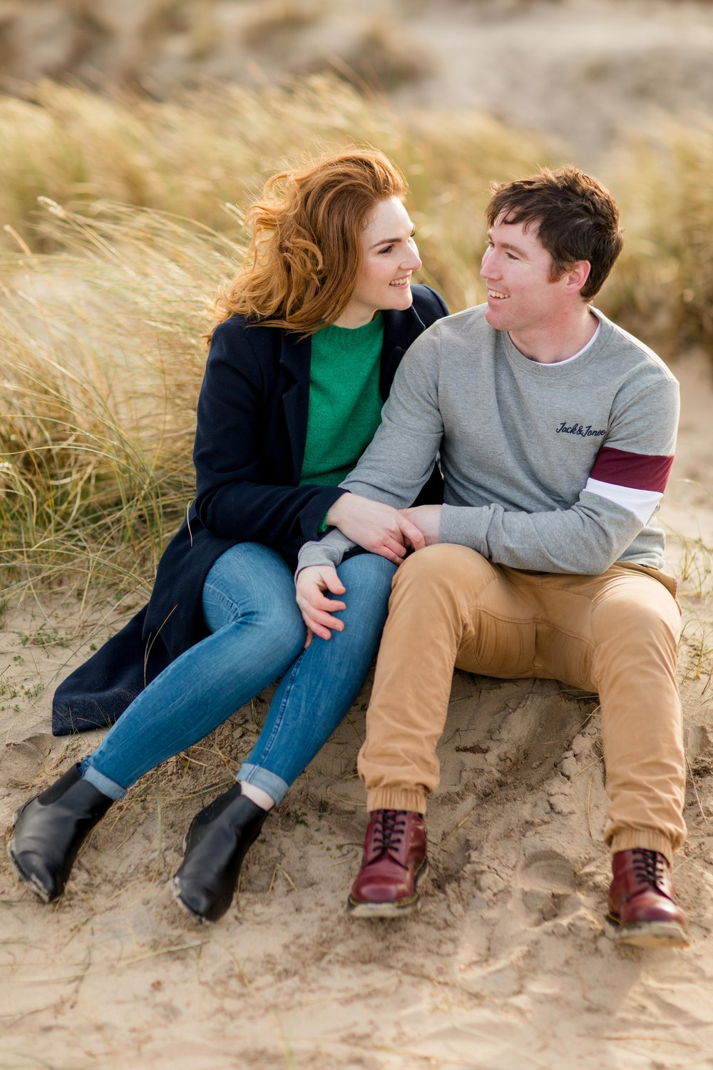 a couple sitting down on a sandy hill on brittas bay in ireland with arms wrapped around eachother wearing casual clothes